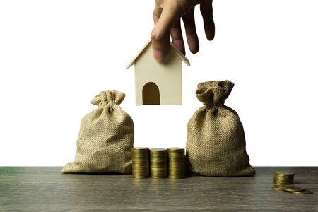 Saving money, home loan, mortgage, a property investment for future concept. A man hand a small residence house over stack of coins pile and money bag on wood table. A sustainable investment.