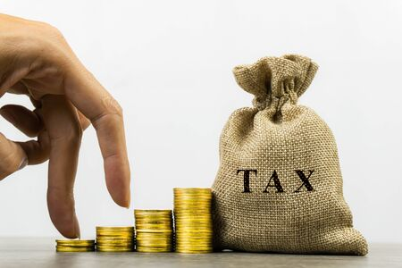 Taxation and Annual tax concept. A man hand on rising stack of coins and tax bag on white background. Depicts a income planning, annual tax deduction. Collect money to pay off debt.