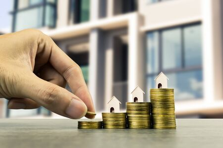 Saving money, home loan, mortgage, a property investment for future concept. A man hand putting money coin over small residence house on stack of coins pile on wood table. A sustainable investment. Stok Fotoğraf