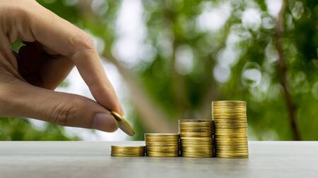 Making money and money investment concept. A man hand holding coin over stack of coins on wood table with nature background. Depicts long-term investment And wealth and financial stability. Stok Fotoğraf