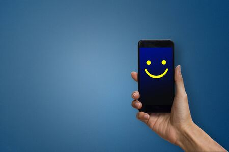 Conceptual the customer responded to the digital survey. The client showing mobile phone screen with happy face. Depicts that customer is very satisfied. Service experience and satisfaction concept. Stok Fotoğraf - 131794012