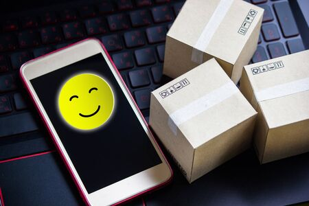 Conceptual the customer responded to the survey. The happy face smile icon  in smartphone after shopping online. Depicts that customer is very satisfied. Service experience and satisfaction concept. Stok Fotoğraf