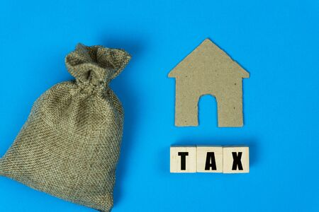 Taxation and Annual tax concept. A message on wooden block with a small house paper cut and money bag  on blue background. Stok Fotoğraf