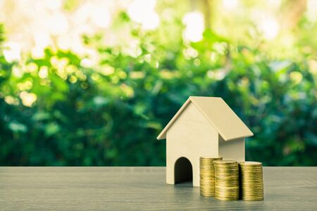 Property investment, Home loan, reverse mortgage concept. A small house model with stack of gold coins on wooden table with nature background and empty space at left hand for your text. Stok Fotoğraf