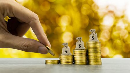 Making money and money investment, Savings concept. A man hand on rising stack of coins with money bag and golden background. Depicts long-term investment And wealth and financial stability.