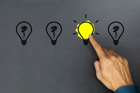 Creative ideas concept. Conceptual different thinking or leadership. A businessman hand choose a one shining light bulb and many light bulb goes out on blackboard.