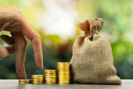 Making money and money investment, Savings concept. A man hand on rising stack of coins with money bag and nature background. Depicts long-term investment And wealth and financial stability.