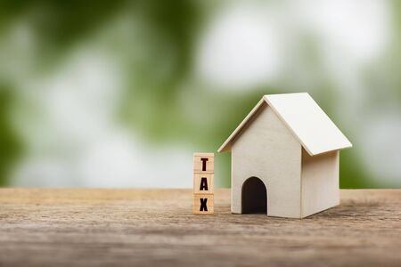 Home or property taxation and Annual tax concept. A small house model with tax on wooden table with nature background.
