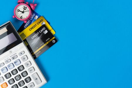 Business and financial concept. Credit card, alarm clock and calculator on black background from top view.