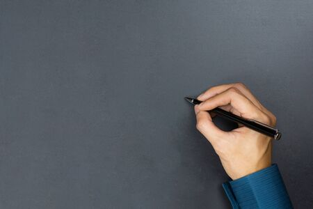 A businessman hand holding black pen and write something on chalkboard. Stok Fotoğraf - 131792530