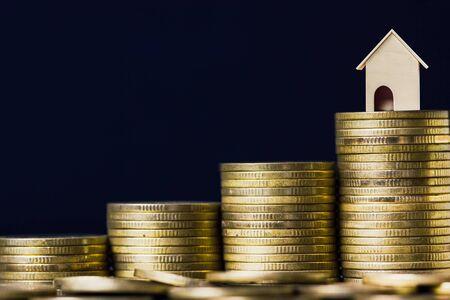 주택 대출, 모기지, 부채, 주택 구매 개념을 위한 저축. 검은 배경을 가진 동전의 상승 스택에 작은 집 모델. 재정 및 주택 교환.