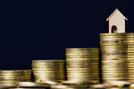 Home loan, mortgages, debt, savings money for home buying concept. A small house model on rising stack of coins with black background. Exchange of finances and houses.