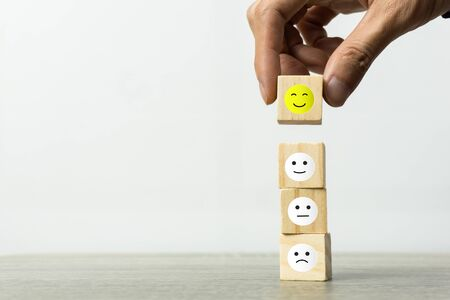 Conceptual the customer responded to the survey. The Businessman hand choose happy face smile icon on top. Depicts that customer is very satisfied. Service experience satisfaction concept. Stok Fotoğraf