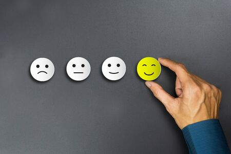 Conceptual the customer responded to the survey. The client using hand choose happy face smile icon. Depicts that customer is very satisfied. Service experience and satisfaction concept.