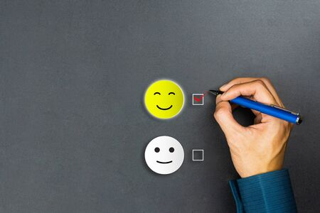 Conceptual the customer responded to the survey. The client using pen checkbox on happy face smile icon. Depicts that customer is very satisfied. Service experience and satisfaction concept.
