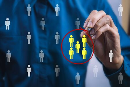 Teamwork or focus niche marketing concept. A businessman write a red line circle around yellow businessman icon.