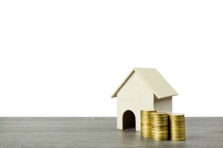 A small wooden house model with stack of golden coins on wood table isolated on white background.