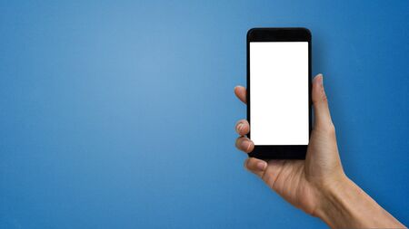 A man hand holding smartphone with white screen and space at left hand on blue background. Stok Fotoğraf