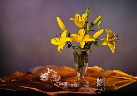 Still life with yellow lily and pearls photo