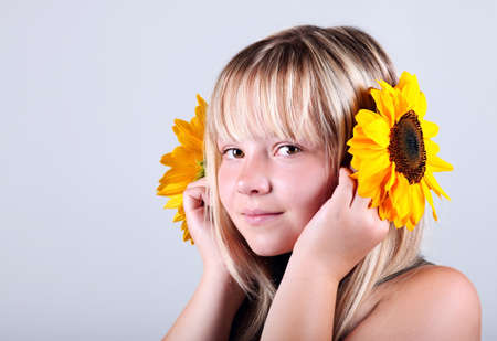 A beautiful happy girl holding a sunflower photo