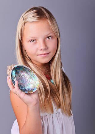 Beautifu young girl holding an open seashell  photo