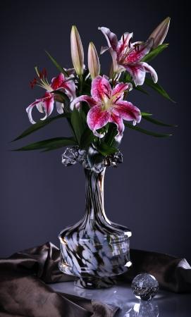 Naturaleza muerta con flores de color rosa lirio en un jarrón de vidrio