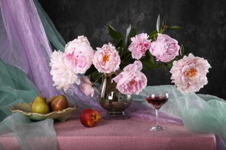Stillleben mit schönen rosa Pfingstrosen und Obst Standard-Bild