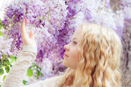 wisteria: Beautiful girl with wisteria flowers in the park. Soft light style color