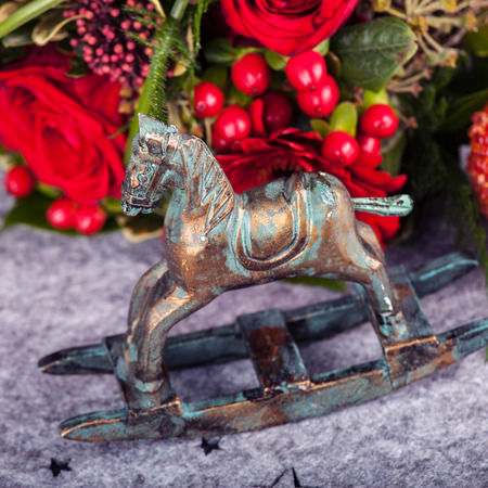Cristmas decoration with Old fashioned wooden seesaw horse and flowers
