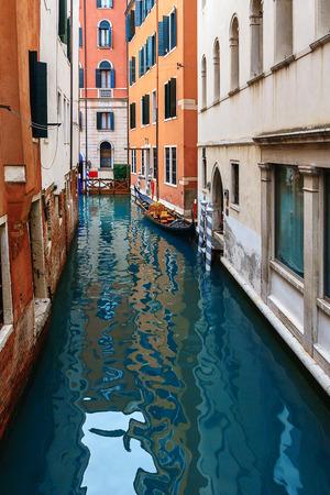 VENICE, ITALY - JANUARY 05, 2018: Typical gondola at narrow venetian canal during winter days, Venice, Italy