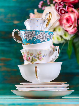 Stack of vintage tea cups on turquoise background