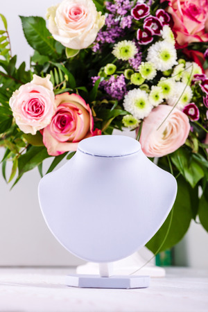 Necklace display on floral backgroung