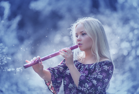 Beautiful young girl playing flute in  the  fairy forest Stock fotó