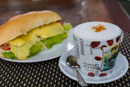 sanwich: A cup of coffee with baguette sanwich.