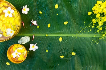 Colorful flower in water gold color bowls decorating and scented water, perfume, on Banana leaf for Songkran Festival or Thai New Year.