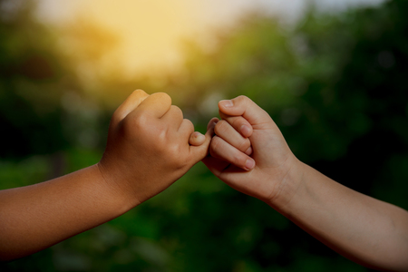 Deux mains s'accrochent au petit doigt concept de promesse Banque d'images