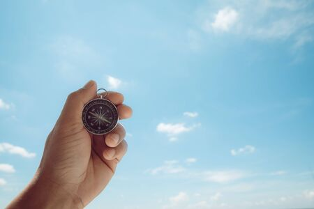 Male hands holding a compass on the sky background