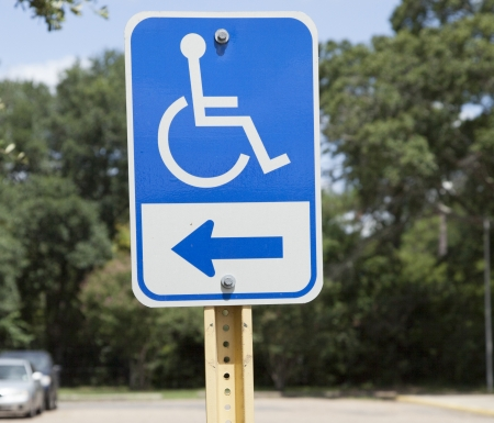 Blue handicapped parking sign in almost empty parking lot Stock Photo - 22359890