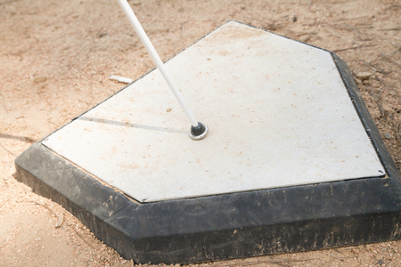 White cane on home base surrounded by dirt