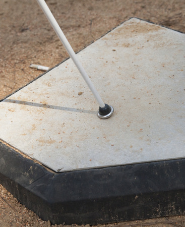White cane on home base surrounded by dirt photo