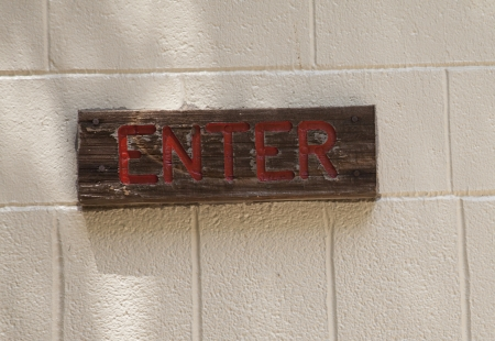 Close up of wooden enter sign on brick background Stock Photo - 22502724