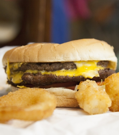 tots: Close up of double cheeseburger surrounded by onion rings and tator tots Stock Photo