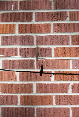 Vertical image of single clothes pin on a laundry line against a red brick wall Stock Photo