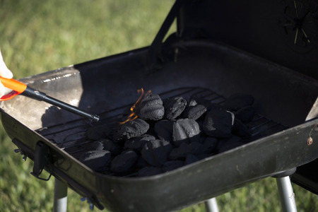 Person starting barbecue grill flame