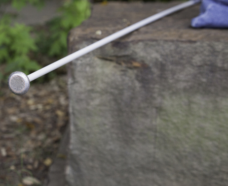 white cane: Bottom of white cane of blind person resting on rock