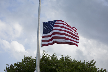 American flag at half mast for mourning and holidays Stock Photo