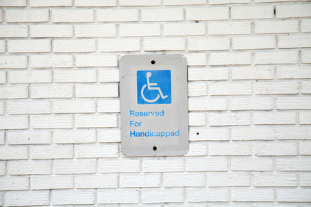 Handicapped parking sign on white brick background