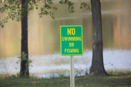 risky behavior: No swimming sign in front of a public lake