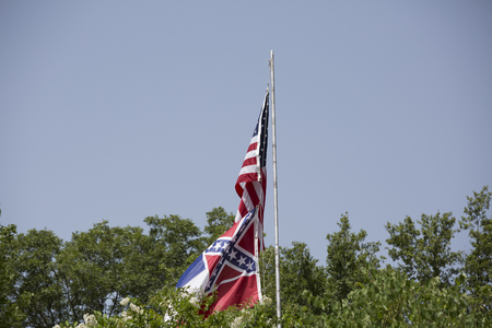 United States and Mississippi state flags flowing in the wind Stock Photo