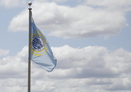 South Dakota state flag waving in blue sky Stock Photo